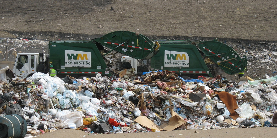 Photo shows two garbage trucks dumping their contents into a landfill.