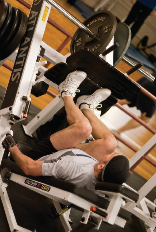 This photo shows a man exercising on a leg press machine at a gym.