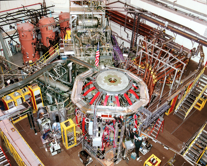 This photo shows the outside of the fusion reactor of the National Spherical Torus Experiment at the Princeton Plasma Physics Laboratory. The reactor, which sits in a large room, is connected to numerous tubes and instruments.