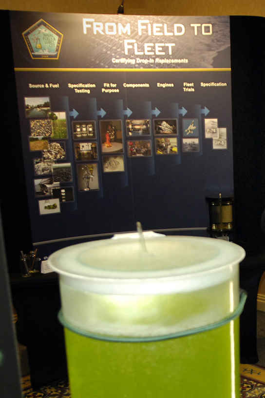 "A photo of a large container of green fluid, with a display in the background with the heading ""From Field to Fleet""."
