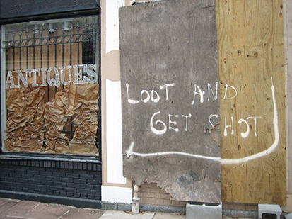 A photo of a damaged home from Hurricane Katrina with a sign posted on the fence that reads, Looters Will Be Shot