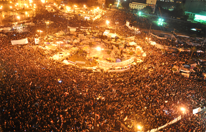 Photo of a crowded Tahirir Square in Cairo, Egypt where many people in the crowd are waiving Egyptian flags in the air