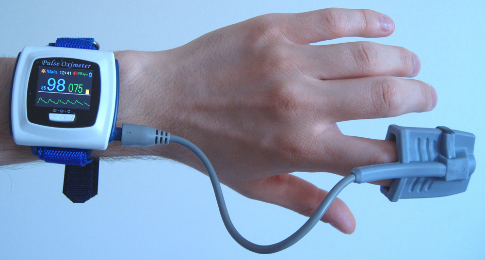 A person is measuring the amount of oxygen in blood and metabolic rate using a pulse oxymeter. The pulse oxymeter is strapped to the person's wrist, and the index finger is inside the clip.