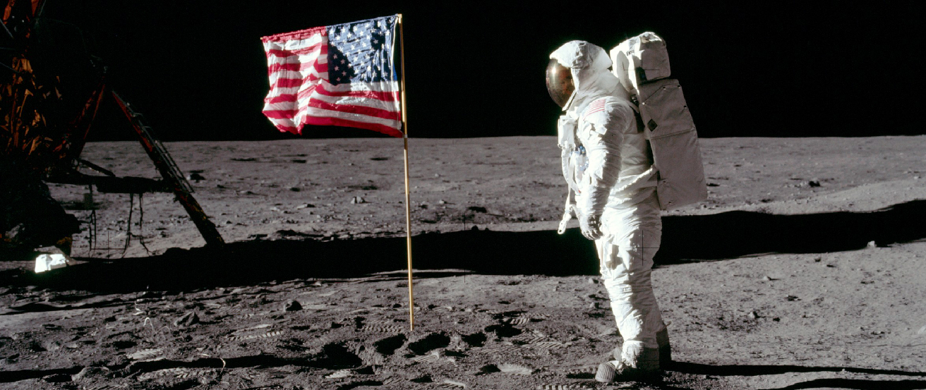 "Edwin ""Buzz"" Aldrin on the Moon. Photograph showing the second man to walk on the Moon facing the American flag erected by the astronauts at the Apollo 11 landing site."