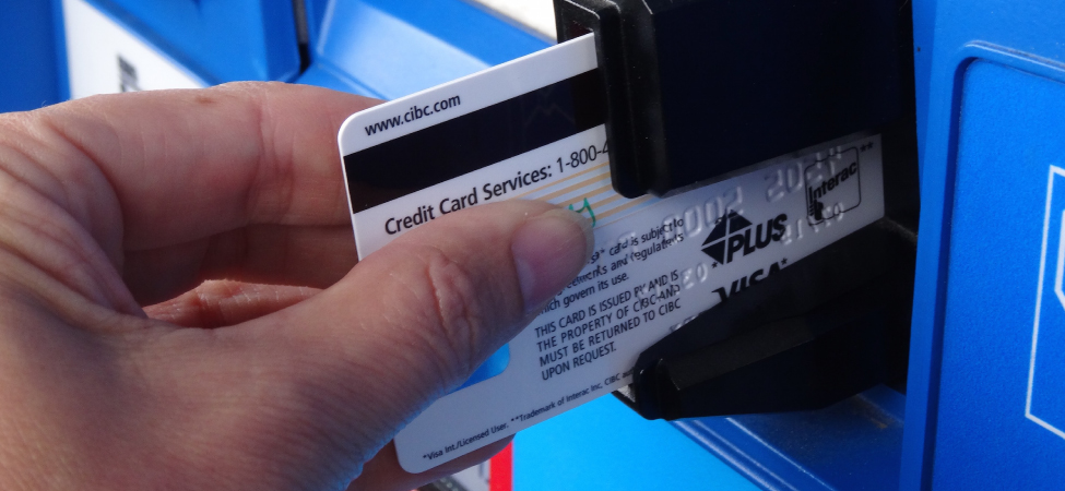 Figure is the photo of the credit card inserted half-way into the slot of the banking machine so that the black magnetic strip is visible.