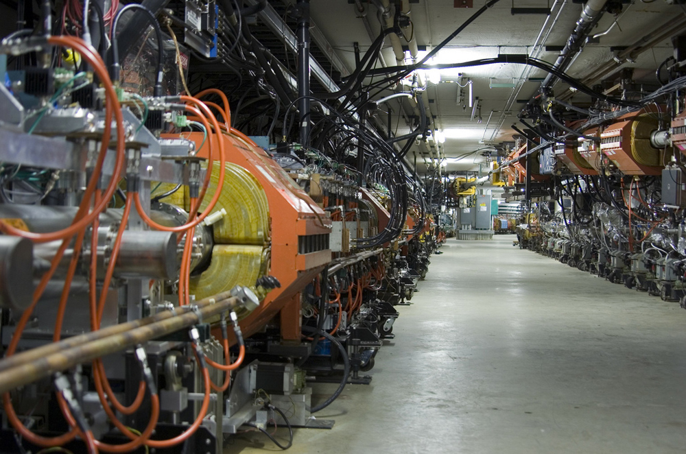 A view of a section of the accelerator at Fermilab. Down each side of a long corridor are tubes surrounded by orange magnets. Lots of tubes and wires and other electronics are visible.