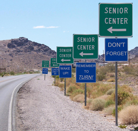 "Five sets of road signs, the top one green and the bottom one red in each set, are shown along the right-hand side of a road in a desert setting. The green signs all read ""Senior Center"" and feature an arrow pointing left. The blue signs, from front to back, read ""Don't Forget,"" ""Remember to [u]Turn![/u]"", ""Wake Up!"", ""Lunch Only $4,"" and ""Turn Now."""