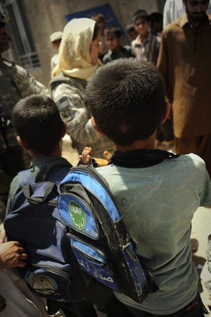 Two Afghan boys with backpacks look toward a smiling U.S. woman in camouflage uniform and yellow headscarf.