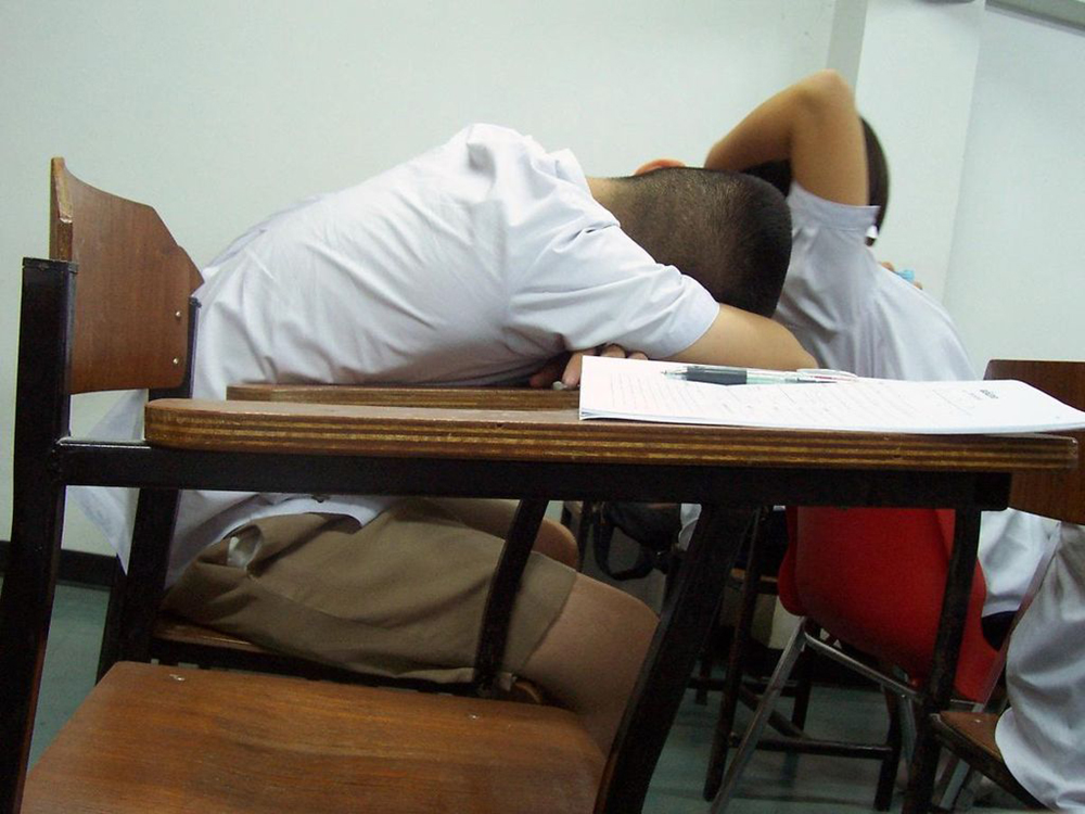 A child asleep at his desk is shown here.