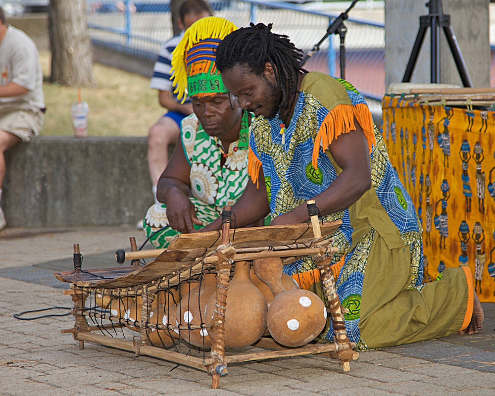 Photograph of two people playing a marimba with gourds as resonance chambers.
