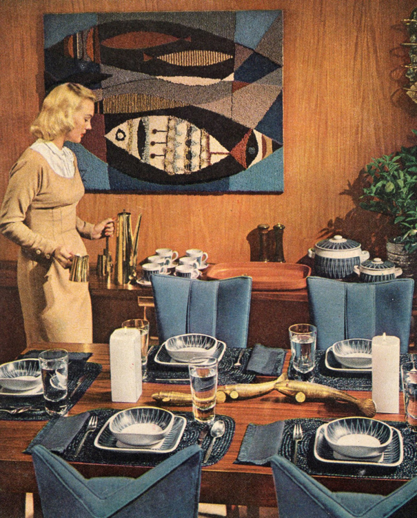 Woman in 1950s or 1960s dress putting coffee on buffet in a formally set family dining room.