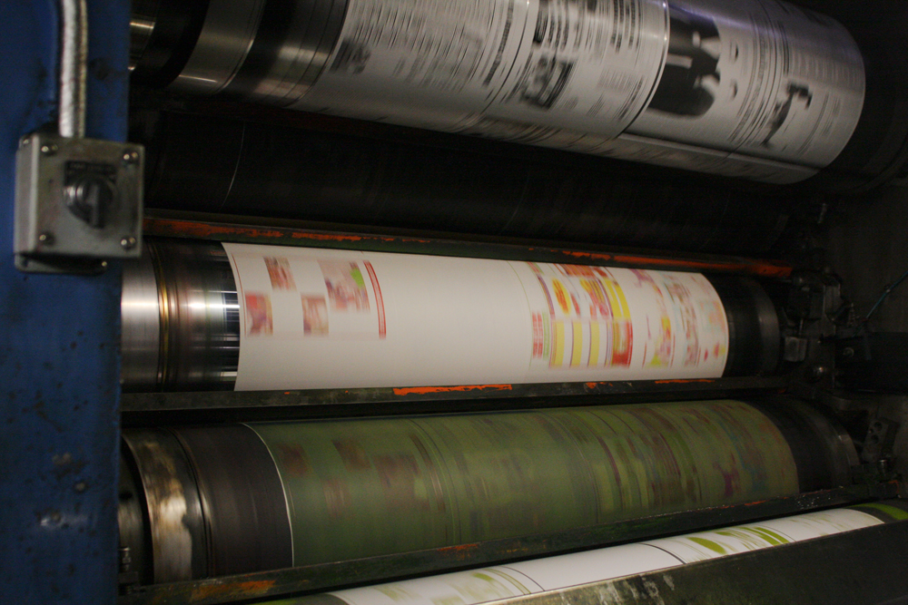 Pages of newspaper are shown flowing through a printing press.