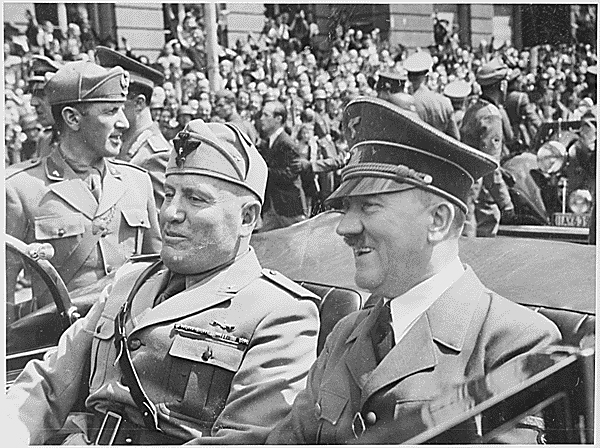 Adolf Hitler and Benito Mussolini are show riding together in a car.