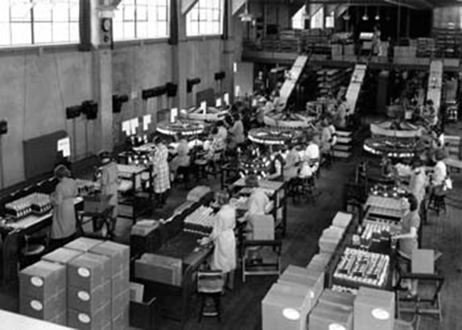 A photograph shows a warehouse full of people working with machines along assembly lines.