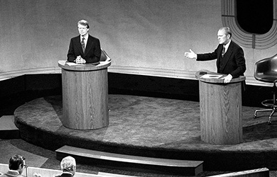 A photograph shows Gerald Ford and Jimmy Carter engaged in debate from two lecterns. Ford is speaking and gesturing toward Carter with one hand.