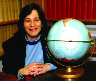 A photograph is shown of Susan Solomon sitting next to a globe.