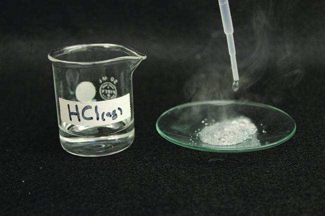 "A photo shows a beaker that contains a clear, colorless liquid. It is labeled, ""H C l ( a q )."" Beside the beaker is a watch glass with a dropper above it. The dropper is releasing liquid into a fizzing liquid. The fizzing liquid is releasing a white gas."