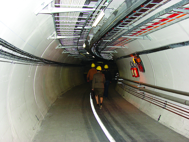 "Two photos are shown and labeled ""a"" and ""b."" Photo a shows an aerial view of the Large Hadron Collider. Photo b shows a tunnel of concrete with rails on the ground and tubes and wires running along the wall. Two people walk along the tunnel."