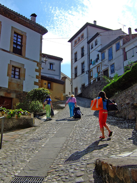 Three female tourists carrying luggage are shown climbing a cobblestone hill.