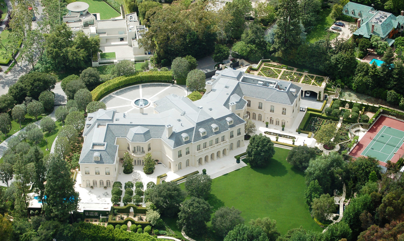 Bird's eye view of a palatial house with a beautifully manicured lawn.