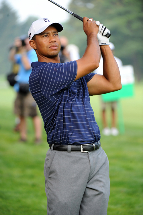 A photo of golfer Tiger Woods holding his golf club up in the air on the golf course after hitting a golf ball