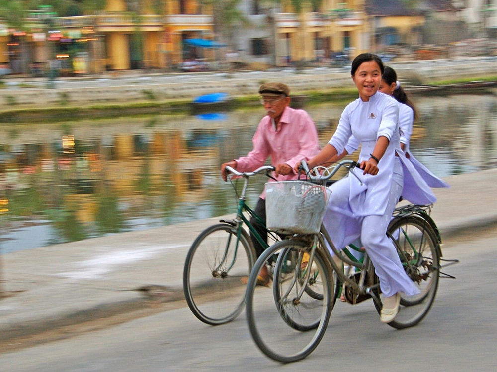 Three people cycling along a canal. The blurred buildings in the background convey a sense of motion of the cyclists.