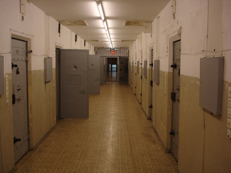 Figure b shows the hallway of a correctional facility.