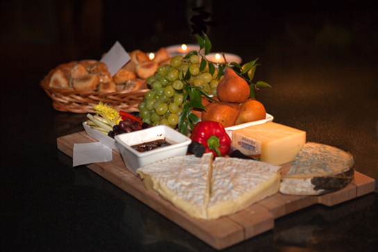Photo shows a variety of cheeses, fruits, and breads served on a tray.