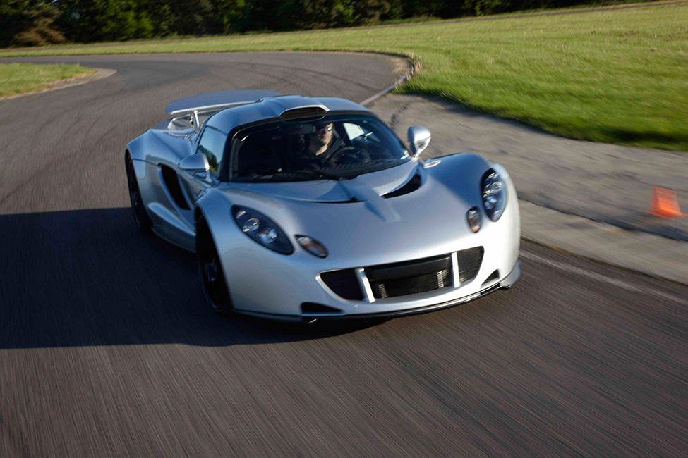 A photo of a Hennessey Venom GT sports car speeding along a winding road.