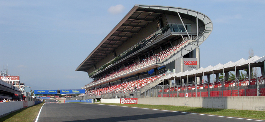 A photo of a grandstand next to a straightaway of a race track.