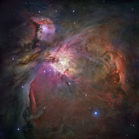 Photograph of the Orion Nebula. This image is dominated by large areas and bright swirls of glowing gas clouds, crisscrossed by dark bands of dust.