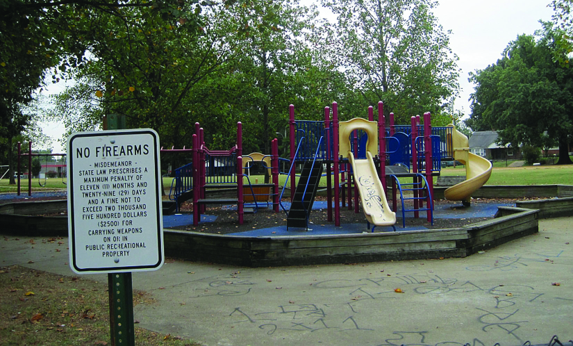 "A photo of a sign that reads ""No Firearms"". A playground can be seen in the background."