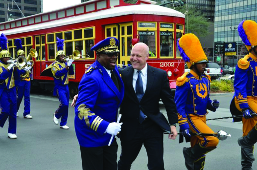 An image of Mitch Landrieu standing in the middle of a group of people who are playing various instruments. A streetcar is in the background.