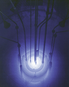 Picture is a photograph of the blue glow in a reactor pool.